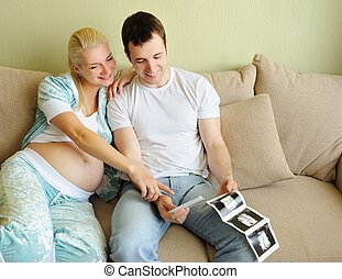 Young couple holding and looking at an ultrasound scan of...