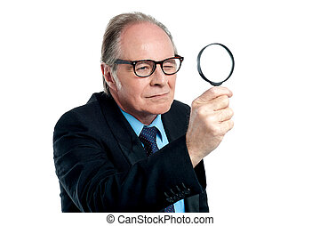 Detective exploring through a magnifying glass - An aged...