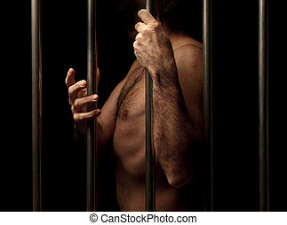 prisoner behind bars gesticulating with hand
