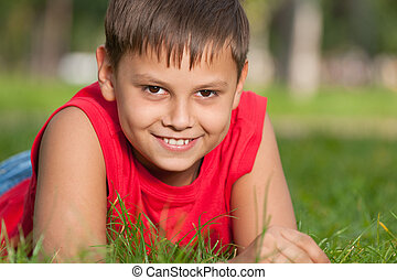 Smiling boy in red on the grass - A cheerful smiling boy in...
