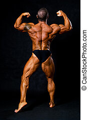 Tanned bodybuilder shows muscles of arms and back in black...