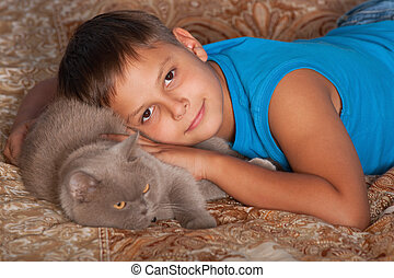 Smiling boy with a cat - A smiling boy is hugging his cat
