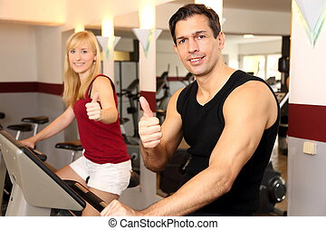 Attractive woman and a man cycling in a gym - A handsome man...