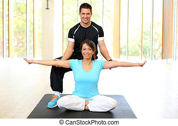 Personal trainer instructing woman in gymnastics -...