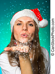 Girl in a Christmas hat blows off snowflakes on blue...