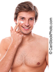 Man with naked torso appliescream on his face