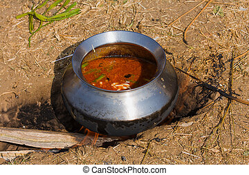 Pot with food on fire, India