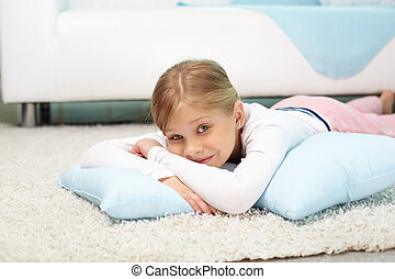 Carefree child - Portrait of lovely girl lying on the floor...