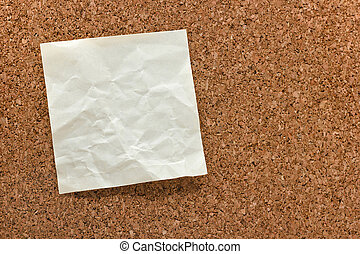 blank crumpled white sticky note on a cork bulletin board