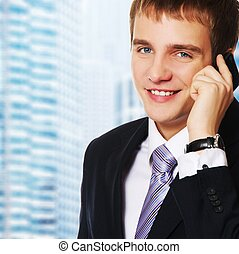 Urban buildings background - Young businessman talking on...