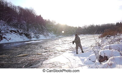 Winter hobby - Man fishing trout in forest river