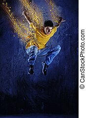 Young man jumping against grunge wall