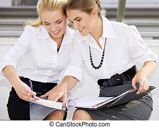 teamwork - picture of two happy businesswomen with documents