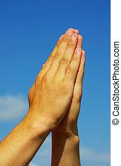 hands in prayer gesture on sky