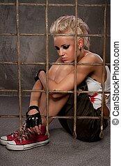 Punk girl behind bars.