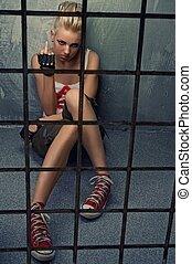 Punk girl showing middle finger behind bars