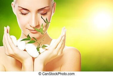 Beautiful young woman holding plant growing up through...