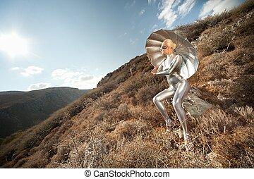 Cyber woman witu umbrella in a mountains.