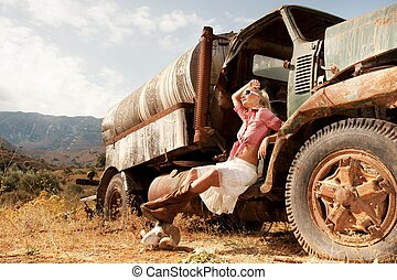 Attractive blond woman near an old truck