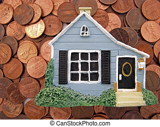homeowner - a toy house sitting on many pennies