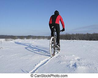 Mountain bike riding through snow