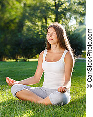 Attractive young woman doing yoga in summer park