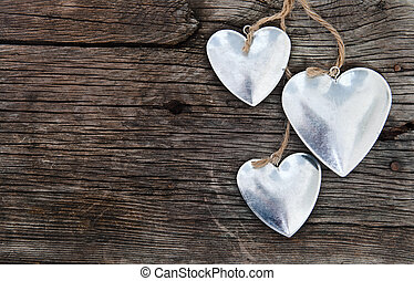 Metal hearts on wooden background. Valentine`s day concept