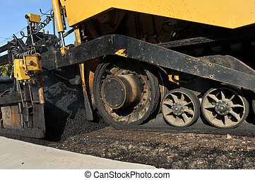 Wheels of an asphalt paving machine on new road - An asphalt...