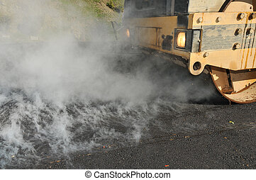 Road roller with steam from asphalt - Steam rised from hot...