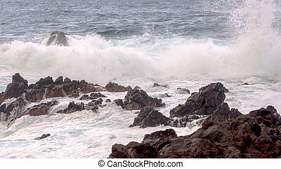 Waves in the sea surrounded by volcanic rocks
