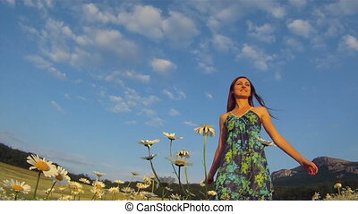 Summer mood - Woman dancing happily in a field of daisies