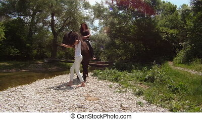 Riding a horse - Two women trying to ride a horse