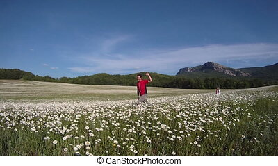 In a field - Father and daughter running across a field of...