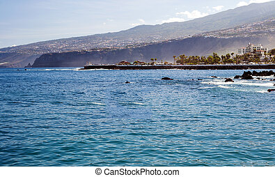 View of a beach with waves in the Spanish town of Puerto de La Cruz, are some rocks in the sea, and the hillside in the background