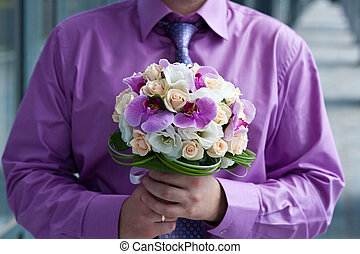 bouquet of orchids - groom holding beautiful flowers bouquet...