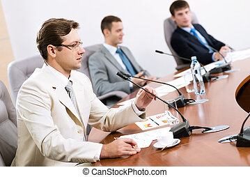Portrait of a businessman, said into the microphone, in the...