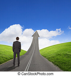 Concept of the road to success with a businessman standing...