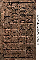 Ancient Mayan hieroglyphs carved on a stone tablet