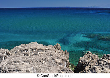 Deep blue sea and volcanic rocks