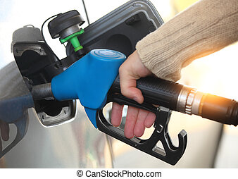 Mans hand refilling the car with a gas pump - Close up of a...