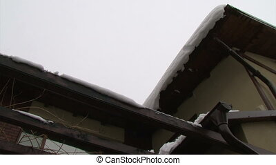 Snow melting and falling from roof - Snow melting and...