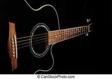 Black acoustic guitar over black background