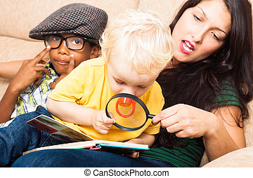 Child exploring book - Young woman and children reading book...