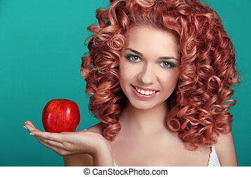 Portrait of young beautiful woman with coloring glossy hair holding red apple