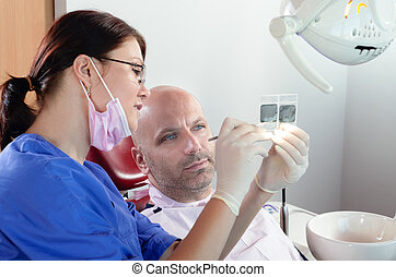 X-ray check - The dentist and his patient are examining a...
