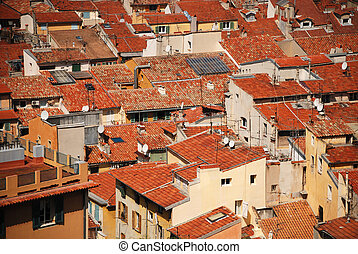 Equal red tile roofs in old residential district of Nice