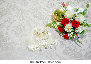 wedding day - a pair of wedding rings and bridal bouquet of...