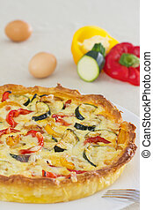 Vegetarian quiche with cat bell pepper, zucchini and eggs on...