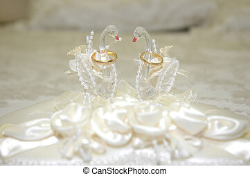 wedding day - a pair of wedding rings in a swan-shaped...