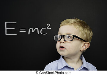 Smart young boy stood in front of a blackboard - Smart young...